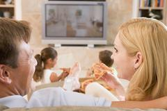 couple enjoying pizza in front of tv - stock photo