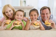 Family eating cheeseburgers together Stock Photos