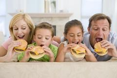 family eating cheeseburgers together - stock photo