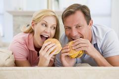 couple enjoying burgers together - stock photo