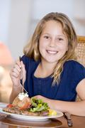 young girl eating meal,mealtime - stock photo