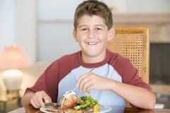 young boy eating meal,mealtime - stock photo