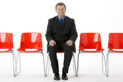 Businessman Sitting In Row Of Empty Chairs - stock photo