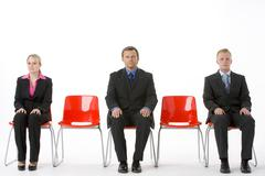 Three Business People Sitting On Red Plastic Seats Stock Photos