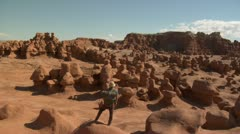 Man stands on Boulder goblin Valley Utah Stock Footage