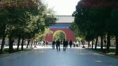 People walk in cypress trees park,China Beijing red door ancient buildings. Stock Footage