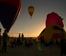 Spectators watching hot-air balloons being filled and lifting off Stock Footage