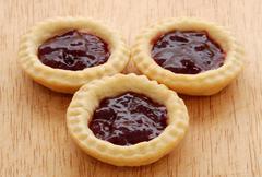 Three tasty jam tarts on a wooden table Stock Photos