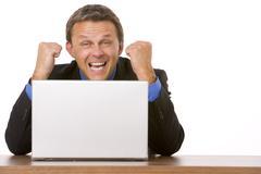 Businessman cheering at laptop Stock Photos