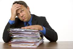 Stock Photo of businessman overwhelmed by paperwork