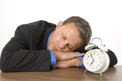Businessman asleep on desk by an alarm clock Stock Photos
