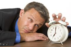 Businessman leaning on desk watching clock Stock Photos