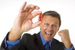 Businessman holding two red dice Stock Photos