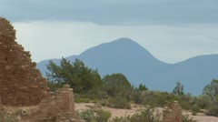 Zoom out shot of mountains revealing ruins  at Hovenweep national Monument Stock Footage