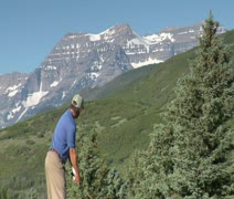 Man tees off on golf course with snowy mountains in distance Stock Footage