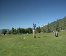 Jib shot of man teeing off on golf course with snowy mountains indistance Stock Footage