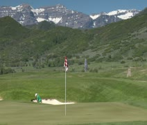 Man chips out of sand trap  to green with snowy mountains in distance - stock footage
