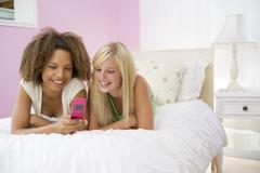 teenage girls lying on bed using cellphone - stock photo