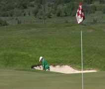 slow-motion shot as  Man chips out of sand trap  to green with snowy mountains - stock footage