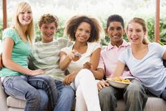 group of teenagers sitting on a couch eating pizza - stock photo