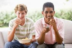 teenage boys sitting on couch eating crisps together - stock photo