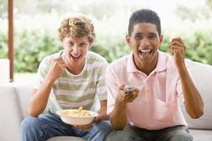 Teenage boys sitting on couch together Stock Photos