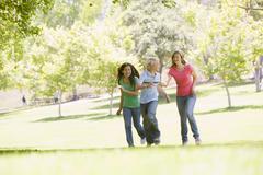 Teenagers running through park Stock Photos