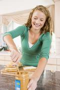 Teenage girl making peanut butter sandwich Stock Photos