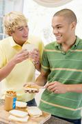 Teenage boys making sandwiches Stock Photos