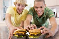 Teenage boys eating burgers Stock Photos