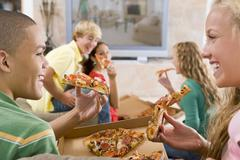 teenagers hanging out in front of television eating pizza - stock photo