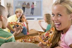 Teenagers hanging out in front of television eating pizza Stock Photos