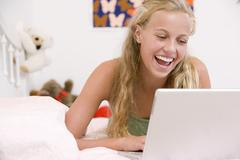 Teenage girl lying on her bed using laptop Stock Photos