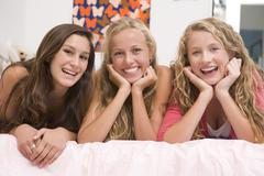 Teenage girls lying on bed using mobile phone Stock Photos
