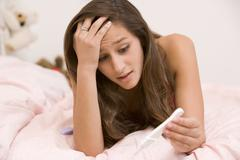 teenage girl lying on her bed with a pregnancy test - stock photo