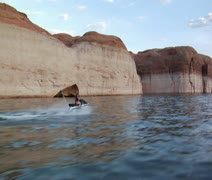 Woman on jet ski with red rock cliffs Stock Footage