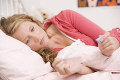 Teenage girl lying on her bed with a pregnancy test Stock Photos