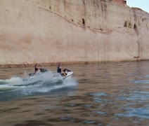 Couple ride jet skis in slow motion with red rock cliffs Stock Footage