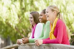 Teenage girls leaning on wooden railing Stock Photos
