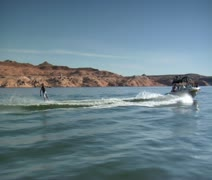 Slow-motion speedboat pulls wake boarder Lake Powell Utah Stock Footage