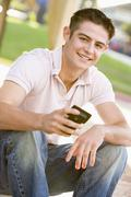 Teenage boy sitting outdoors using mobile phone Stock Photos