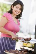 woman cooking on a barbeque - stock photo