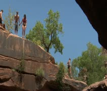 People jump off red rock cliffs into water below Stock Footage