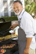 Man barbequing in a garden Stock Photos