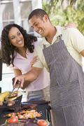 Couple cooking on a barbeque Stock Photos
