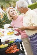 couple cooking on a barbeque - stock photo