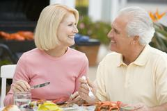 Couple enjoying a barbequed meal in the garden Stock Photos