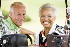 Couple enjoying a game of golf Stock Photos