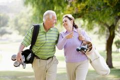 couple enjoying a game of golf - stock photo
