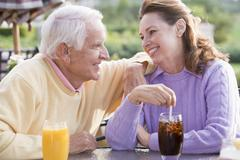 couple enjoying a beverage by a golf course - stock photo